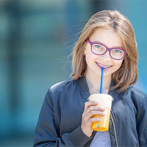 preteen with braces smiling with a drink in her hand