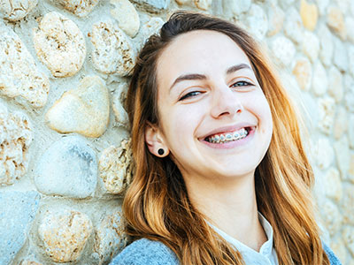 young adult girl smiling in braces